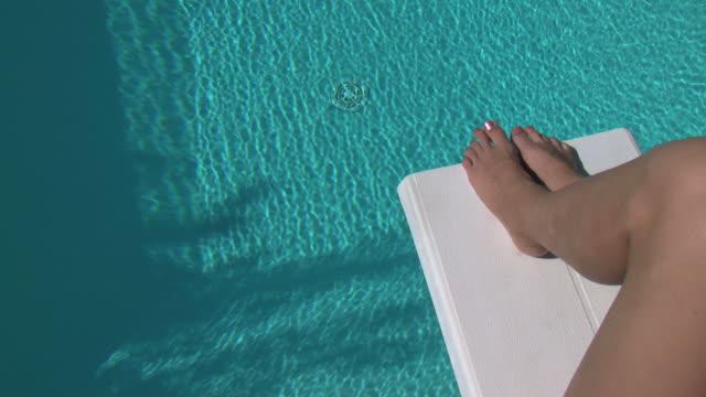 Blond woman sunbathing on the diving board (use of jib)