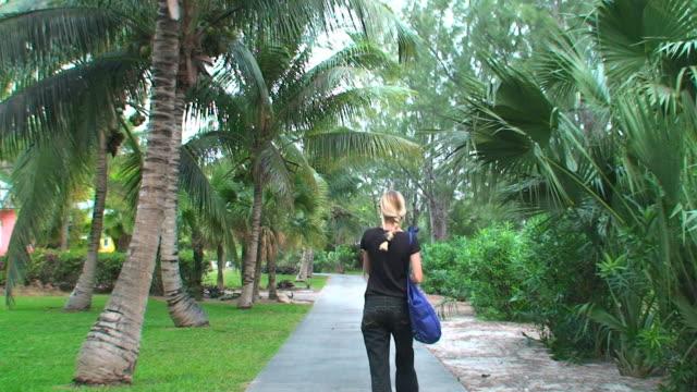 Blond woman walking on a tropical garden