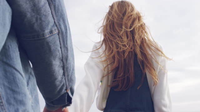 blond woman walking with man while holding hands - holding hands stock videos & royalty-free footage