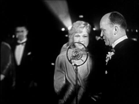 b/w 1928 blonde actress talking into microphone at interference premiere / newsreel - 1928年点の映像素材/bロール