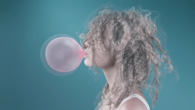 blonde and curly woman blowing bubble gum - gomma da masticare video stock e b–roll
