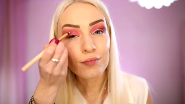 blonde applying make up on face - side hustle stock videos & royalty-free footage