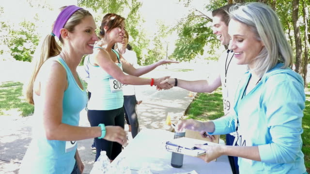 blonde athletic woman registering for 5k or charity marathon race - charity benefit stock videos & royalty-free footage