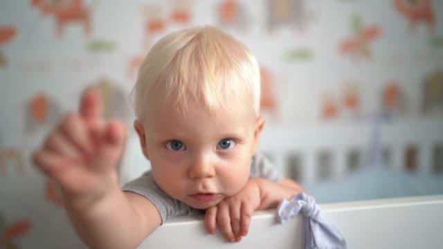vídeos de stock, filmes e b-roll de bebé louro dentro da ucha - apontando sinal manual