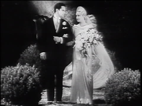vidéos et rushes de b/w 1935 blonde bride + groom standing near bushes looking at each other - trentenaire