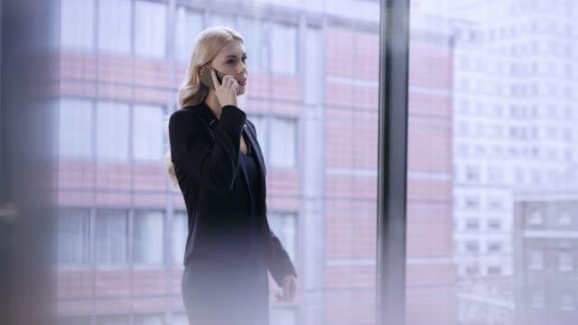 廊下で通話を終了しての距離歩いて金髪ビジネス女性 - 金髪点の映像素材/bロール