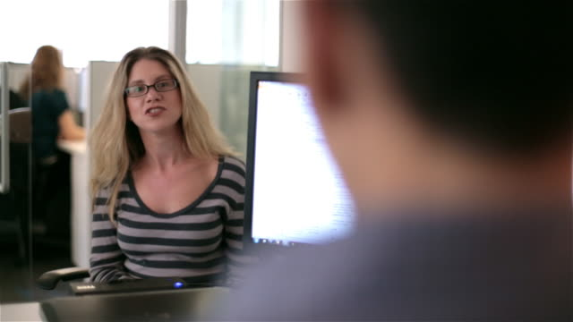 Blonde businesswoman listens, responds to boss in corporate office meeting