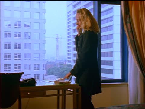 blonde businesswoman standing by window + dialing telephone in hotel room / jakarta - 加入電話点の映像素材/bロール
