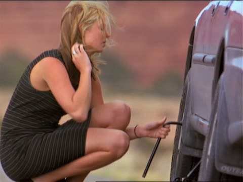 blonde caucasian woman in black dress changes tire on her car - lug wrench stock videos and b-roll footage