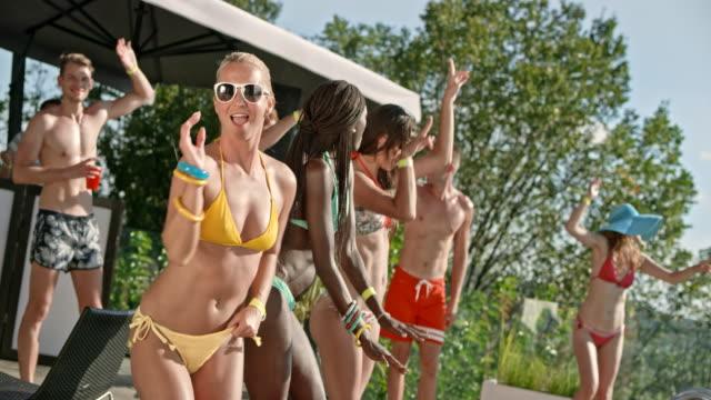 vídeos de stock, filmes e b-roll de mulher caucasiana loira de biquíni amarelo dançando com seus amigos em uma festa na piscina - calção