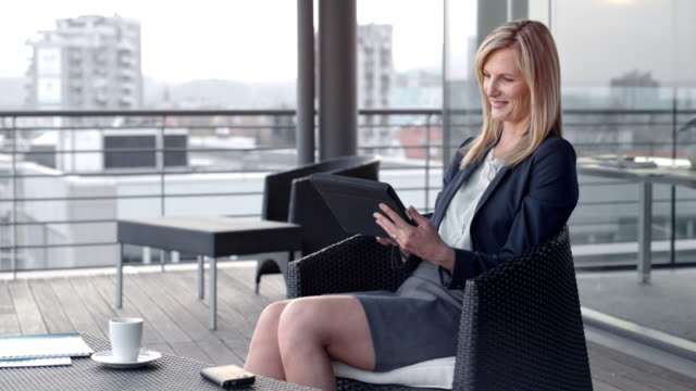 blonde caucasian woman smiling and scrolling her digital tablet on a rooftop terrace in the city - mini skirt stock videos & royalty-free footage