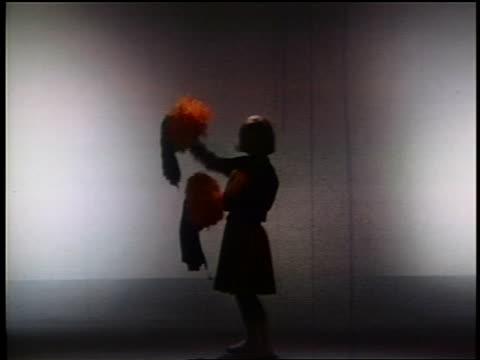 1966 silhouette blonde cheerleader in studio / lights come on + she starts dancing / industrial - cheerleader stock videos & royalty-free footage