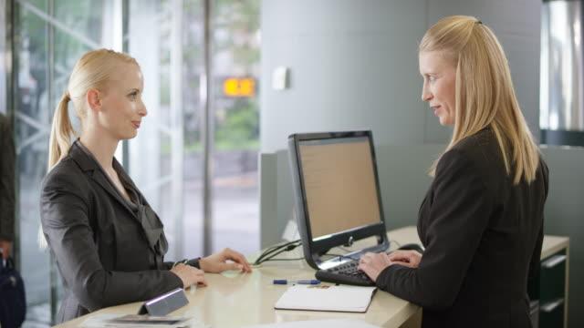 blond kvinnlig kund lyssna på en kvinnlig receptionist som rådgivning till henne - kassörska bildbanksvideor och videomaterial från bakom kulisserna