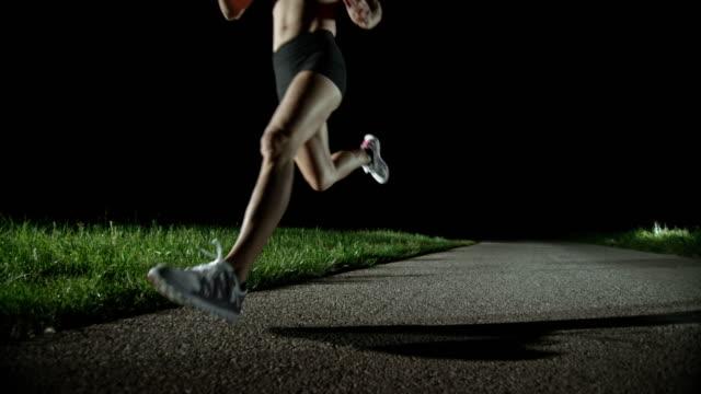 SLO MO PAN Blonde female runner running at night