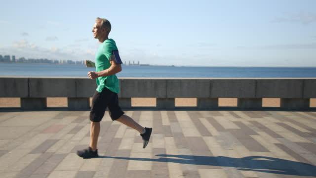 堤防に沿って朝のジョギングにブロンドフィットランナー - 中年の男性一人点の映像素材/bロール