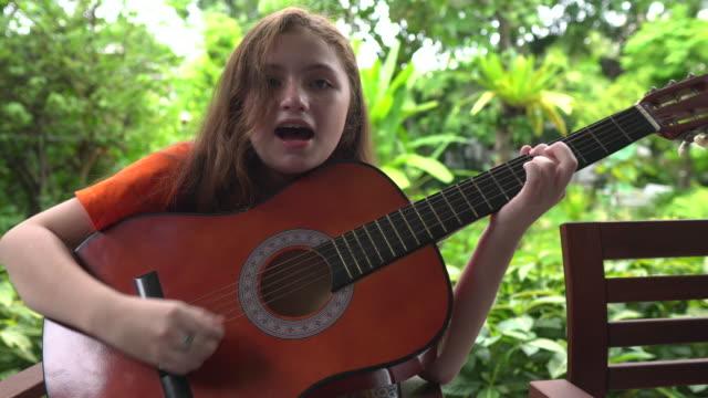 vídeos y material grabado en eventos de stock de chica rubia disfrutando tocando la guitarra - 12 13 años