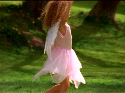 blonde girl in dress + angel wings spinning in grass - angel点の映像素材/bロール