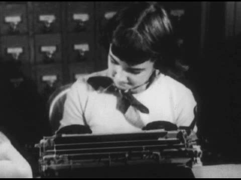 / blonde girl in dress writing on paper / pan to girl at typewriter next to her / high angle shot of young boy at table drawing; adult from behind... - 1951 stock videos & royalty-free footage