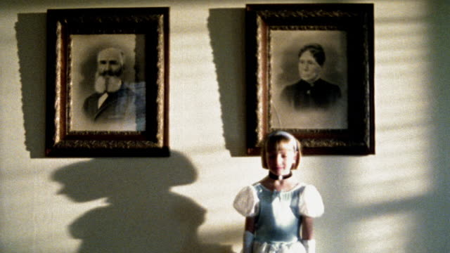 ms portrait blonde girl in fancy dress standing in front of framed portraits of 1800s man + woman - formal stock videos and b-roll footage