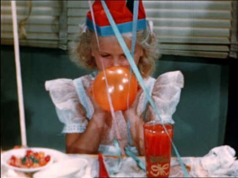 1946 blonde girl in hat blowing balloon + putting it into glass of juice at party / industrial - unfug stock-videos und b-roll-filmmaterial