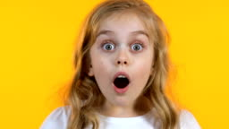 Blonde girl looking extremely shocked hearing news, isolated yellow background