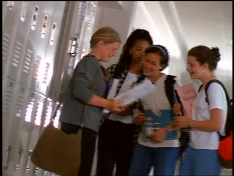 CANTED blonde girl opening locker + showing pamphlet to three teen girls / girls laughing
