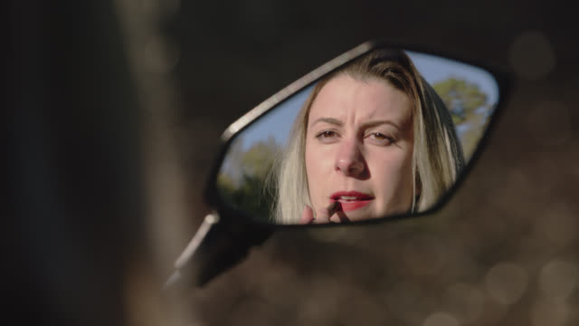 Blonde girl puts on lipstick and pulls helmet on reflected in motorcycle side mirror.