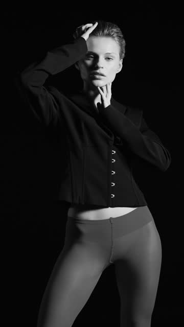 blonde girl stands in a black jacket and tights, touches her face and hair with her hands. black and white video. - tights stock videos & royalty-free footage