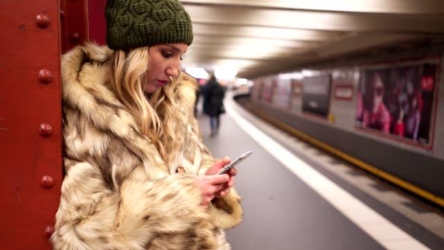 stockvideo's en b-roll-footage met blond meisje met haar smartphone tijdens het wachten voor haar trein - metro passagierstrein