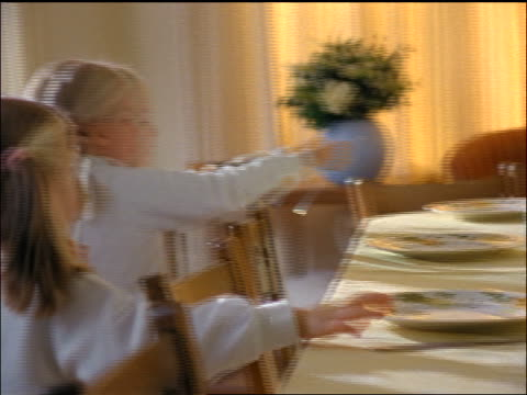 stockvideo's en b-roll-footage met 2 blonde girls setting dining room table with silverware - gedekte tafel