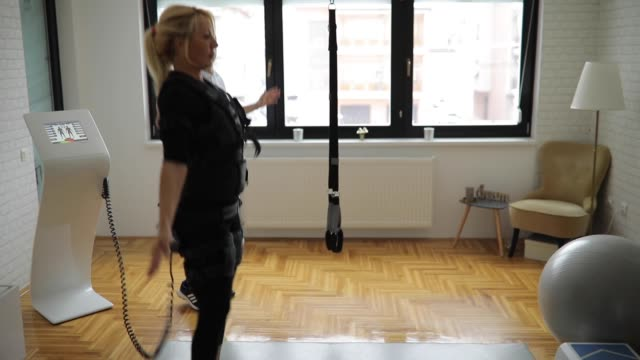 blonde lady exercising with personal trainer on ems training - physiotherapy stock videos & royalty-free footage