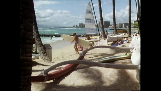 blonde man carries surfboard towards ocean; waikiki beach, 1983 - pacific islands stock videos & royalty-free footage