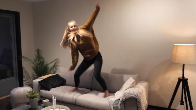 stockvideo's en b-roll-footage met blonde duizendjarige vrouw springt op de bank - generation z