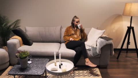 vídeos de stock e filmes b-roll de blonde millennial woman lying on couch and using phone to listen to music - generation z