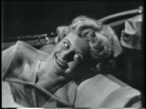 b/w 1958 blonde teen girl smiling as she reclines in passenger seat of convertible - one teenage girl only stock videos & royalty-free footage
