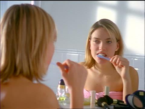 vídeos y material grabado en eventos de stock de blonde teen girl wearing towel looking in bathroom mirror brushing teeth - cepillar los dientes