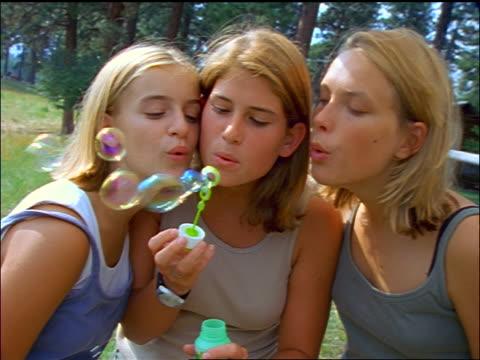 3 blonde teen girls blowing bubbles toward camera / Montana
