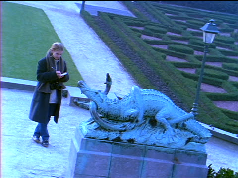blue canted blonde teenage girl standing in park sketching statue of alligator eating serpent - solo adolescenti femmine video stock e b–roll
