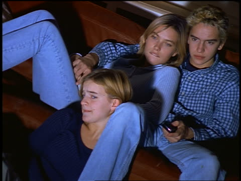 vidéos et rushes de 3 blonde teens lounging on couch watching at something scary on offscreen television - homme dans un groupe de femmes