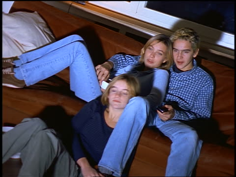 vidéos et rushes de 3 blonde teens lounging on couch watching + laughing at something on offscreen television - homme dans un groupe de femmes