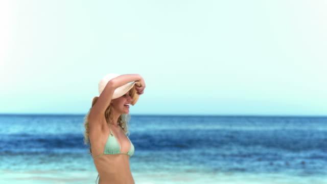 vídeos y material grabado en eventos de stock de blonde throwing her hat in slow motion - sombrero de sol