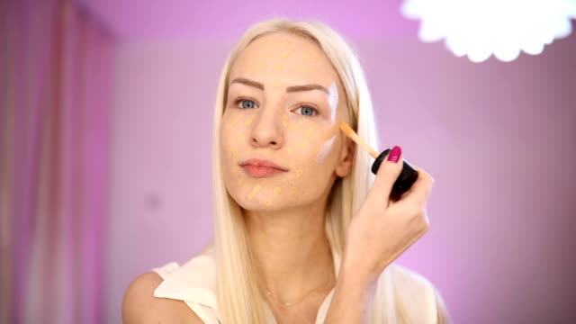 blonde woman applying make up on face - side hustle stock videos & royalty-free footage