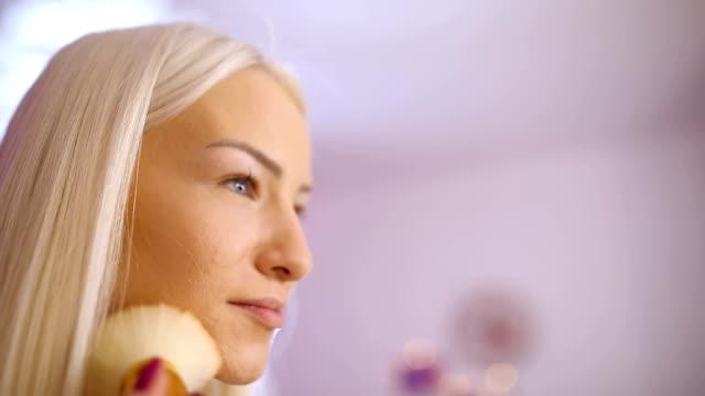 blonde woman applying make up - side hustle stock videos & royalty-free footage