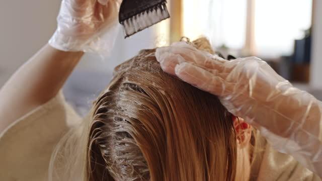 blonde frau färbung haare zu hause - handtuch stock-videos und b-roll-filmmaterial