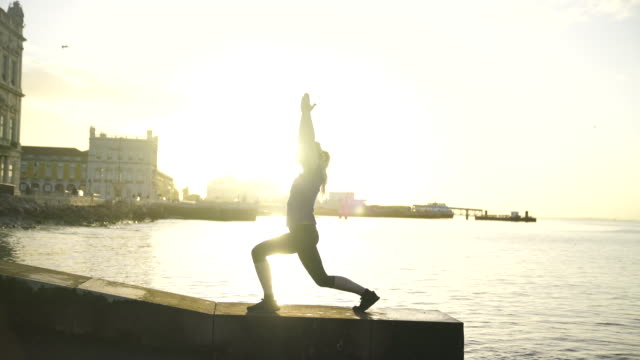 Blonde woman doing yoga moves near the ocean in downtown Lisbon