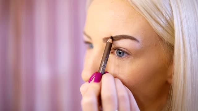 blonde woman drawing eyebrows - eyebrow stock videos & royalty-free footage