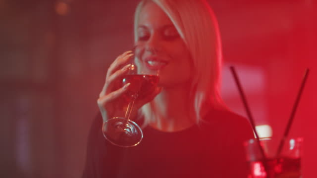 Blonde woman drinking red wine 4K