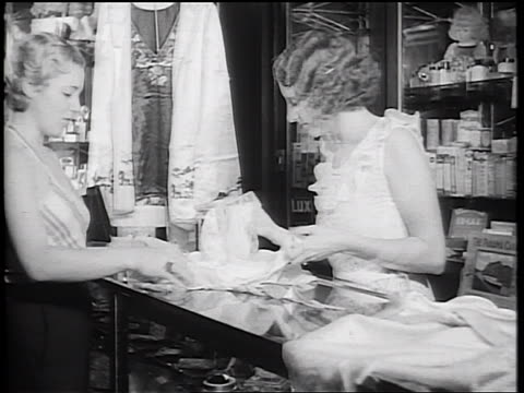 B/W 1934 blonde woman examining clothing with salesperson over counter of cruise ship store