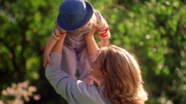 blonde woman holding girl toddler in hat over her head + spinning around outdoors - sonnenhut stock-videos und b-roll-filmmaterial