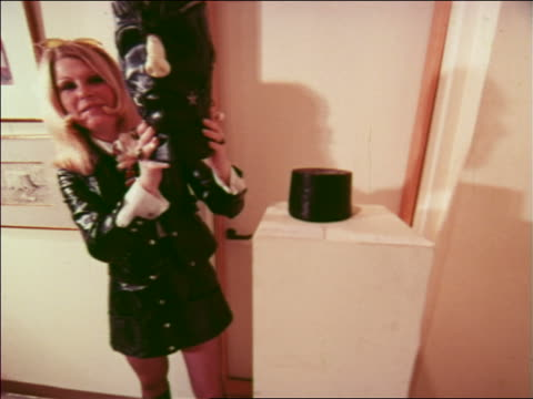 1970 blonde woman holding head of art exhibit in museum / low angle sculptures + buildings outdoors - kunstmuseum stock-videos und b-roll-filmmaterial